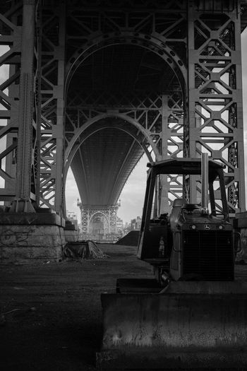 A digger underneath Manhattan Bridge in New York City, New York, USA. Arch Architecture Black & White Black And White Photography Blackandwhite Blackandwhite Photography Bridge - Man Made Structure Built Structure Day Diminishing Perspective Engineering Metallic No People