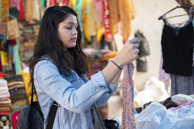 Side view of teenage girl buying clothes in market