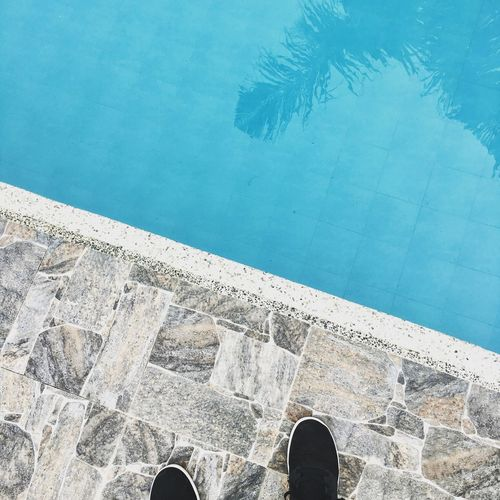 Low section of person standing by swimming pool