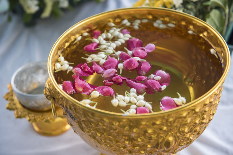 Flowers in gilded container filled with water during songkran festival