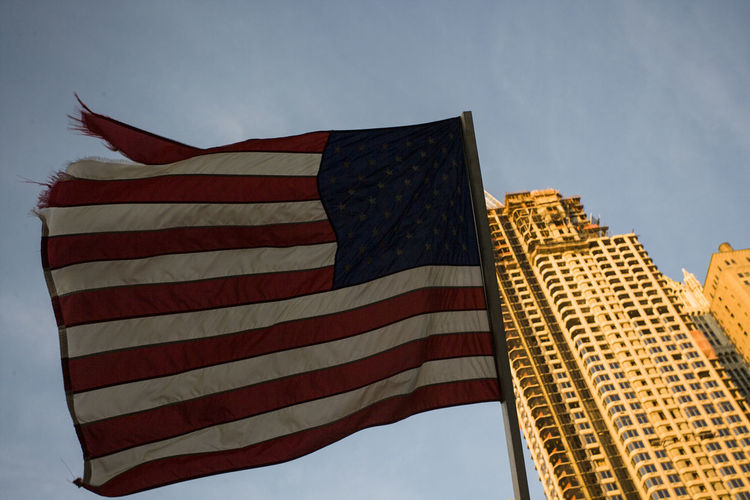 Low angle view of usa flag against sky with skyscraper.