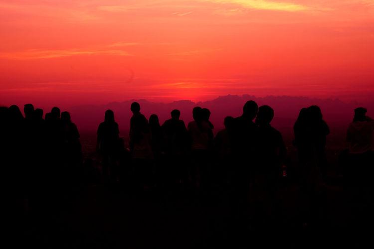 Silhouette people looking at orange sky