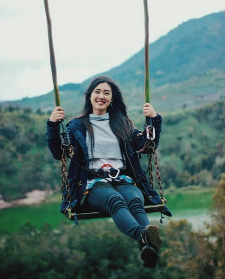 Portrait of smiling young woman on swing