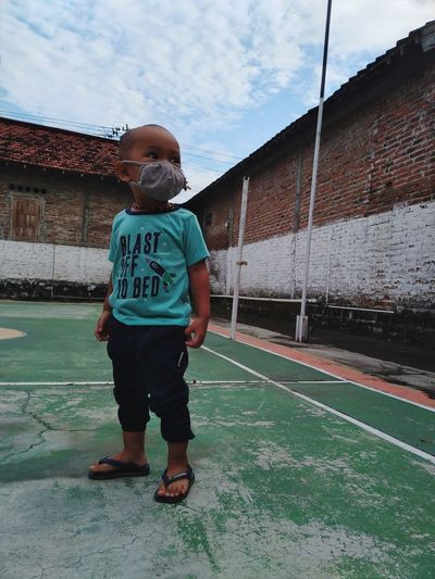 Full length of boy standing on sports court