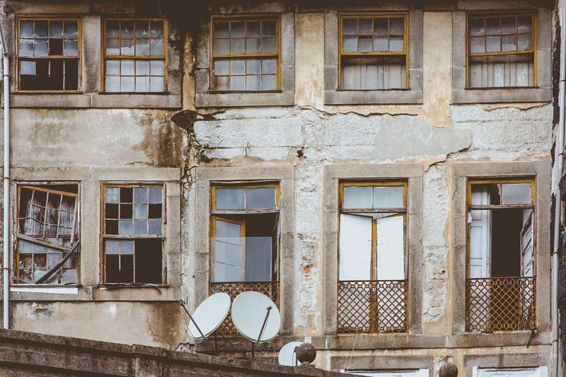 Old devastated dingy front wall house in Porto, Portugal Abandoned Antenna Architecture Balcony Broken Building Exterior Built Structure City Derelict Devastated Development Dingy Empty Glass Home House Investment Left Alone No People Poor  Sat Tv Shabby Squat Wall Window