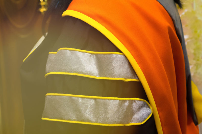 Midsection Of Woman Wearing Graduation Gown