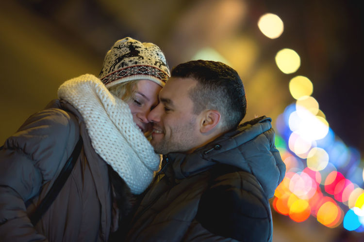 Smiling young couple standing at night during winter