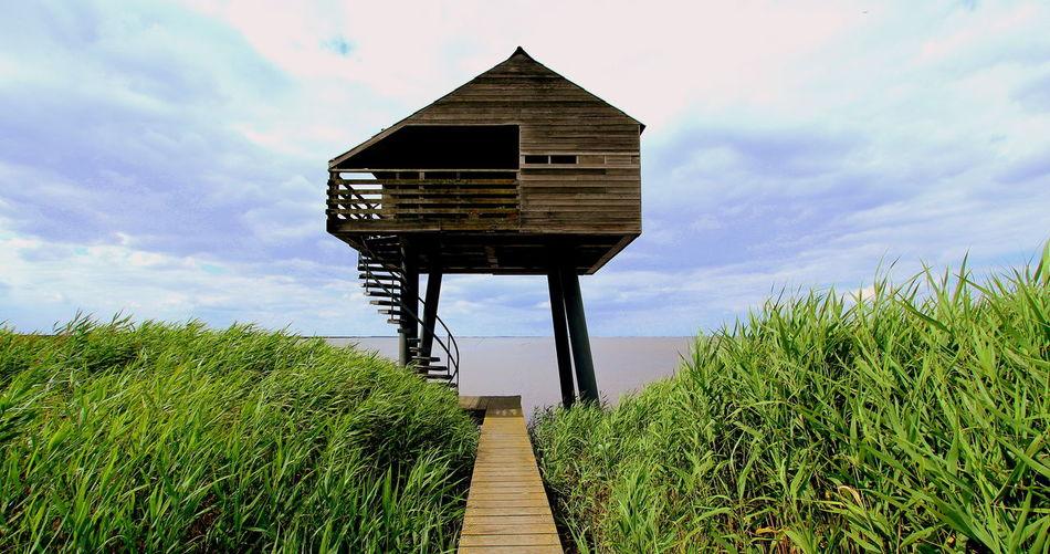 Boardwalk leading towards stilt house by sea against sky