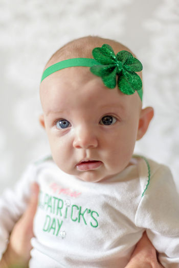 Cropped hand holding cute baby girl wearing green headband