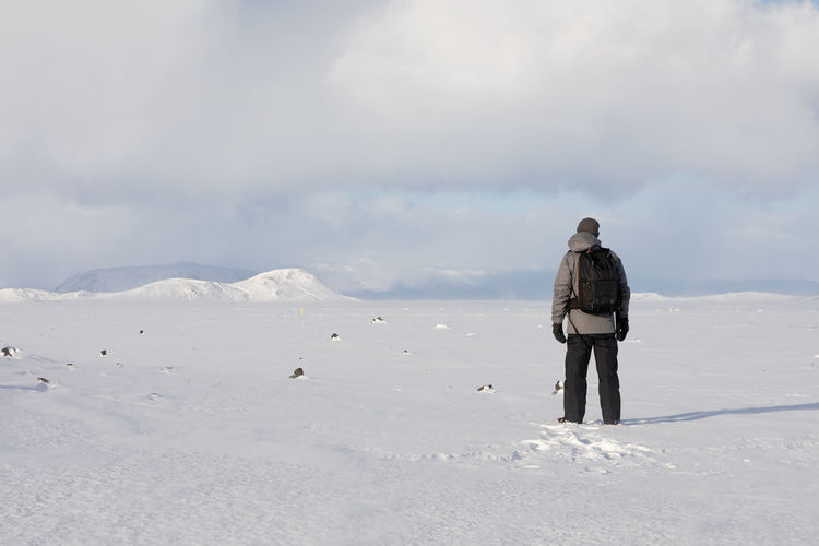 Rear view of man standing on snow covered land