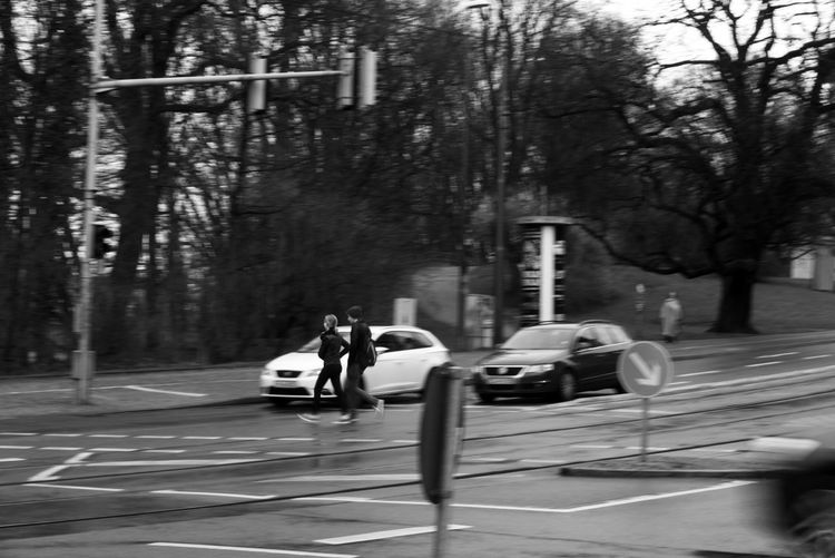 Blackandwhite City City In Motion Day Land Vehicle Lifestyles Men Mode Of Transportation Motion Motor Vehicle Nature Outdoors People Plant Real People Road Road Marking Sign Street Transportation Tree Two People Women
