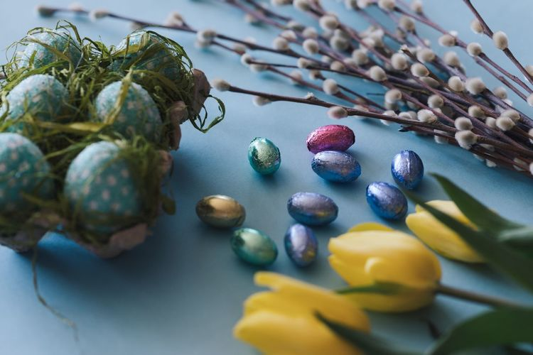 Close-Up Of Easter Eggs And Yellow Tulips On Table