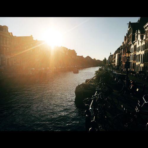 Sun shining through buildings in city