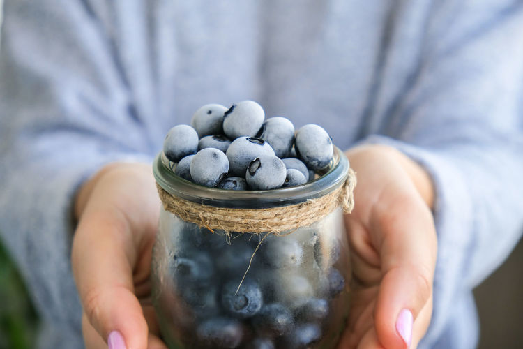 Woman holding bowl with frozen blueberry fruits. harvesting concept. female hands collecting berries