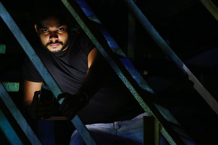 Portrait of young man in front of metal gate at night
