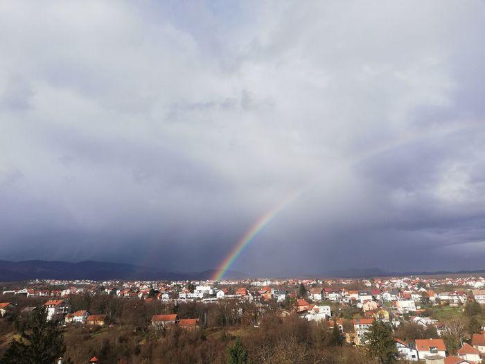 Rainbow over town against sky