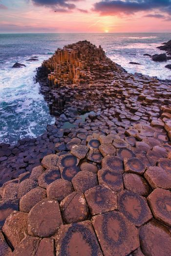 Rocks on shore during sunset