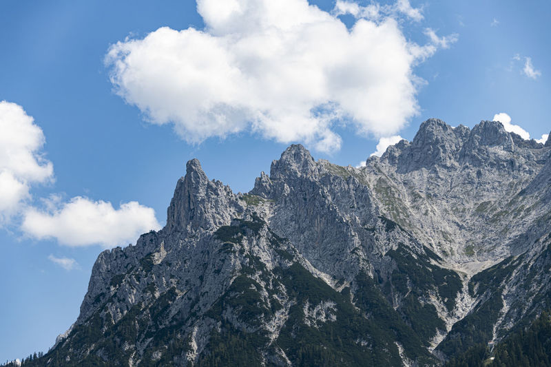 Alps mountain peaks with a green vegetation and the blue cloudy sky