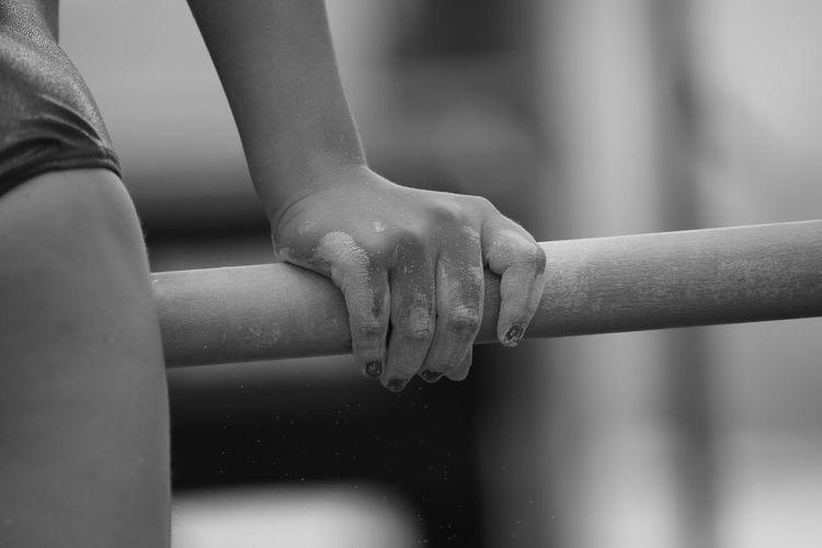 Cropped image of gymnast holding horizontal bar