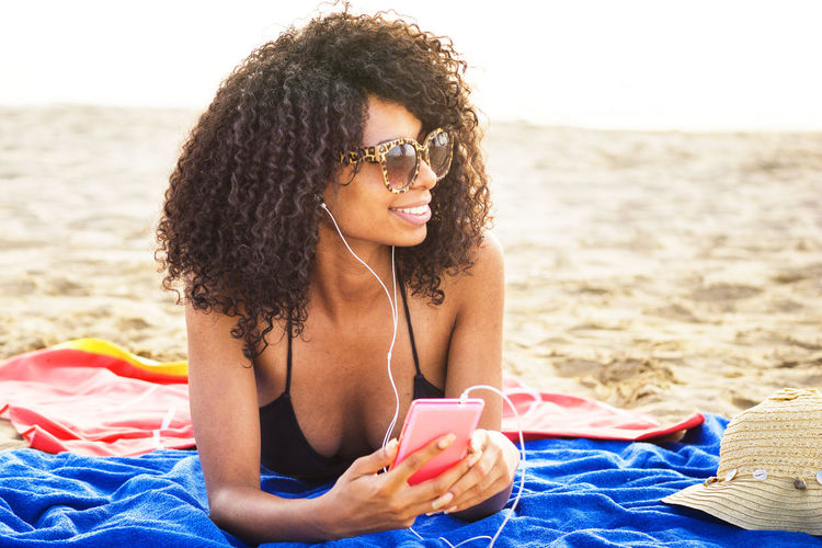 Smiling Young Woman Listening Music While Lying At Beach