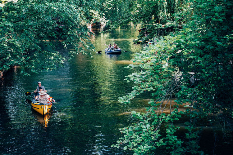 People on boat in river against trees