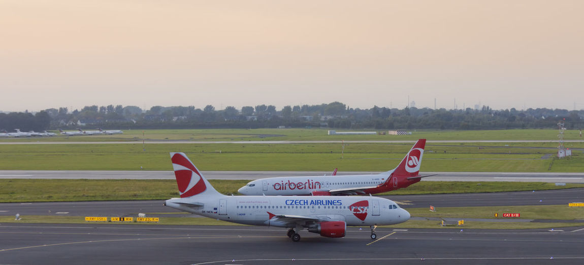 Arriving Boeing 737 of Air Berlin and leaving Airbus A319 of Czech Airlines on International Airport in Düsseldorf, Germany. Both aircrafts are short- to medium-range commercial passenger jets and strong competitors in aviation market. Airbus Airbus A319 Business Czech Airlines Plane Runway Transportation Aerospace Industry Air Berlin Air Vehicle Aircraft Airfield Airline Airplane Airport Airport Runway Boeing Boeing 737 Business Finance And Industry Commercial Airplane Competition Full Length Side View Success Two Objects