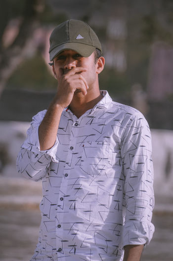 Man looking away while standing against blurred background