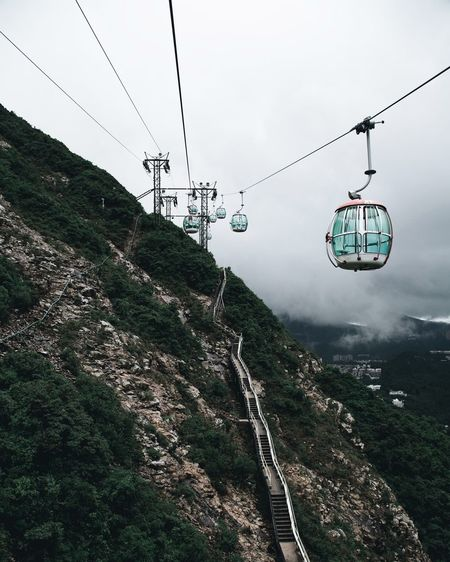Overhead cable cars by mountain against cloudy sky
