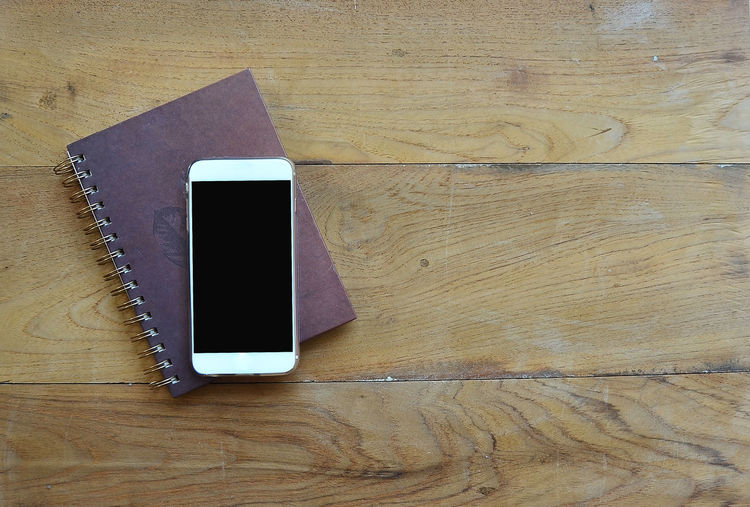 Directly above shot of smart phone diary on wooden table