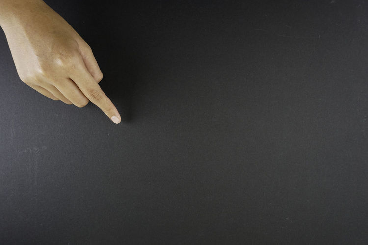 Close-up of hand holding black background