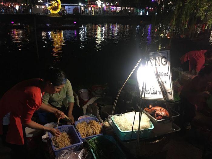 Real People Night Men For Sale Market Market Stall Lifestyles Food Outdoors Retail  Sitting Women Water Freshness Adult People Night Market In Vietnam Vietnam Riverside Asian Culture Asia Riverside