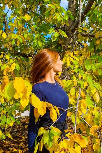 Young woman standing against yellow tree