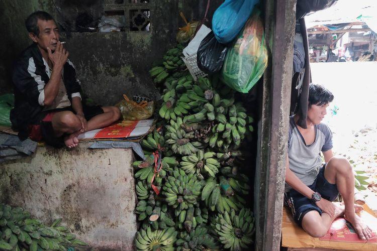 Man smoking while sitting by bunch of bananas at market
