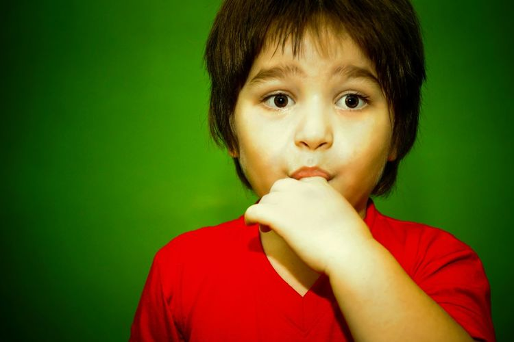 Close-up of boy with his finger in mouth