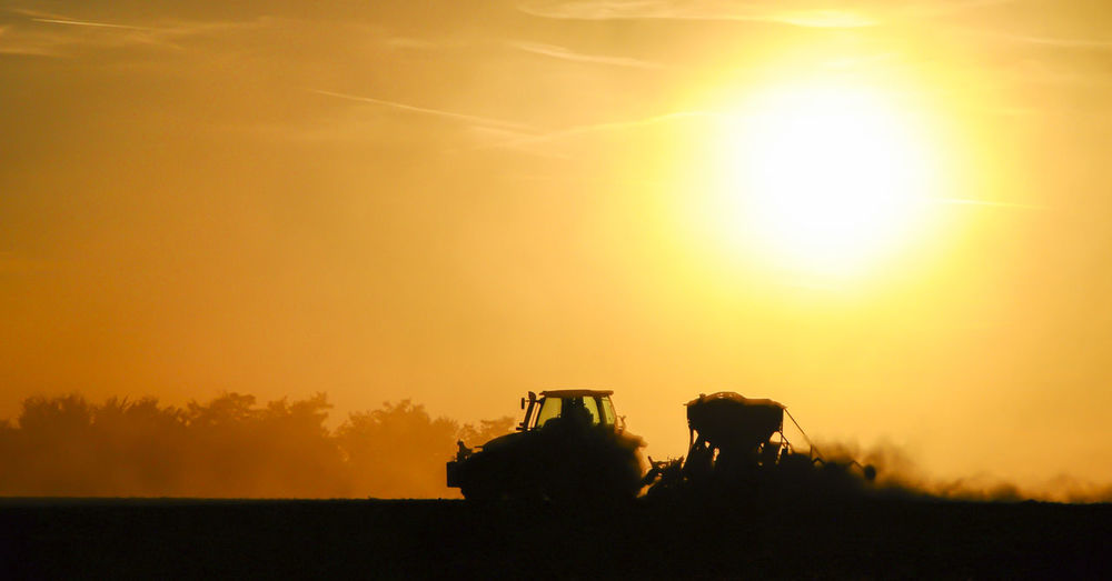 Silhouette of a tractor sowing seeds in a field in a cloud of dust against the background.