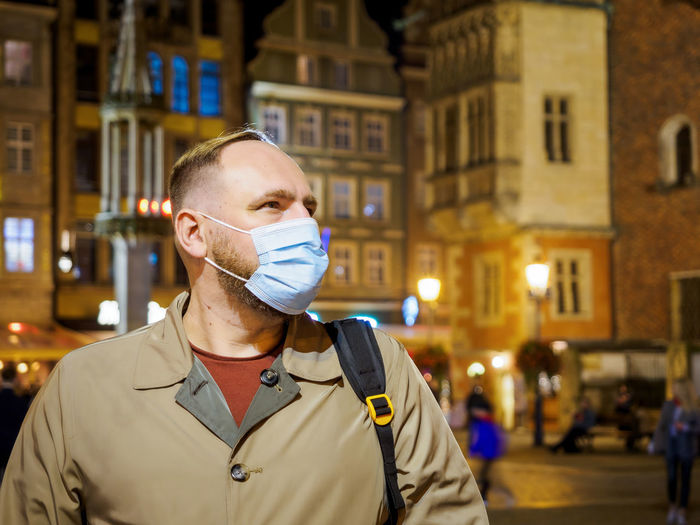 Adult man wearing mask walking in a night european city. mask is a necessary in new normal reality