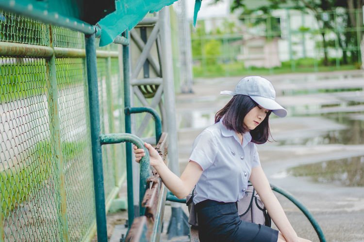Side view of thoughtful young woman looking down while sitting on bench in park during rainy season