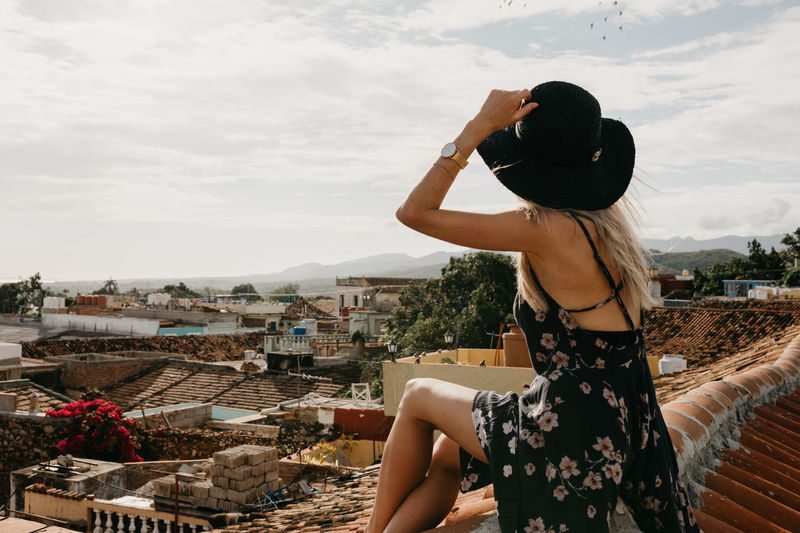 Side View Of Young Woman Looking At Cityscape While Sitting On Rooftop Against Sky During Sunny Day