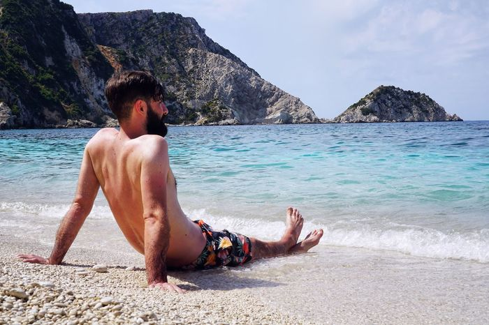 EyeEm Selects Sea Shirtless Beach One Person Rock - Object Real People The Week On EyeEm Colour Of Life Beach Life Outdoors Nature One Man Only Beauty In Nature Sky Sand Full Length Young Adult Sitting Men Scenics Holiday Lifestyles Real Photography Travel Destinations