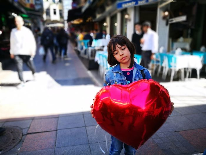 Girl Holding Heart Shape Balloon While Standing On Footpath In City