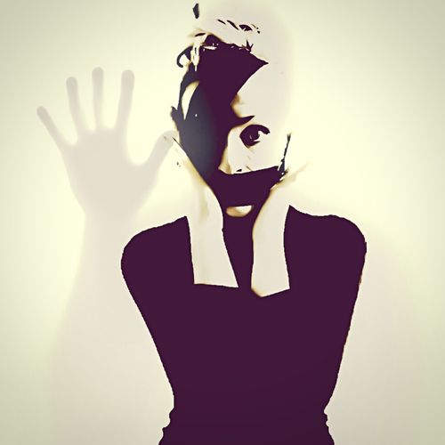 Woman covering face with duct tape with hand shadow in background