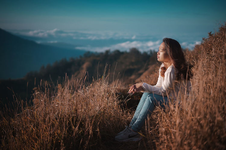 Side view of woman sitting on high field against sky