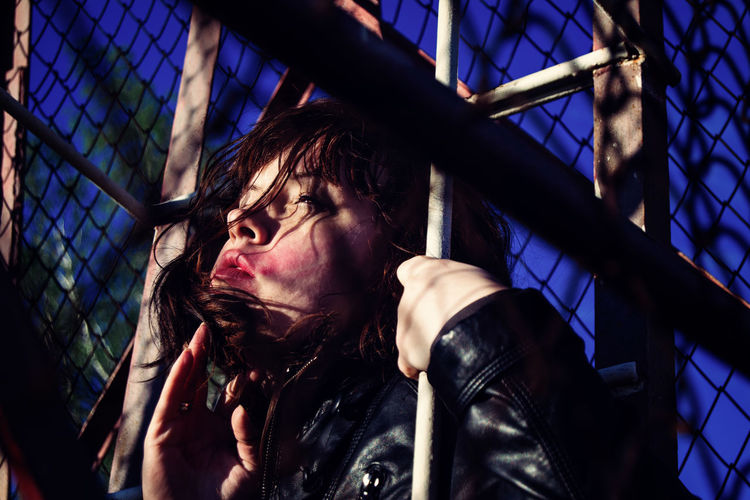 Low Angle View Of Young Woman Looking Through Fence