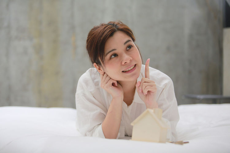Close-up of smiling woman gesturing while lying on bed with model house