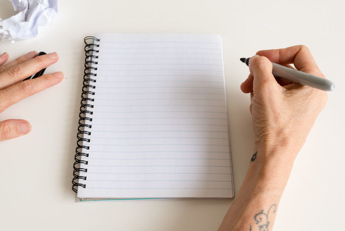 Woman holding pen over blank notepad Blank Body Part Book Finger Hand High Angle View Holding Human Body Part Human Finger Human Hand Indoors  Nail Note Pad One Person Paper Pen Publication Real People White Background Writing Writing Instrument