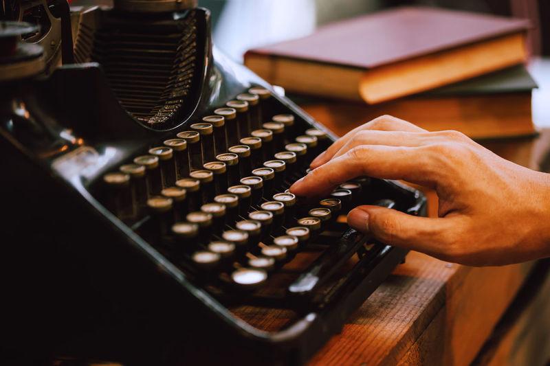 Cropped hand of man using typewriter