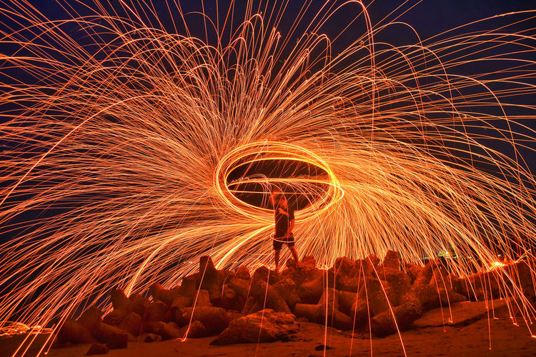 Man spinning wire wool at beach