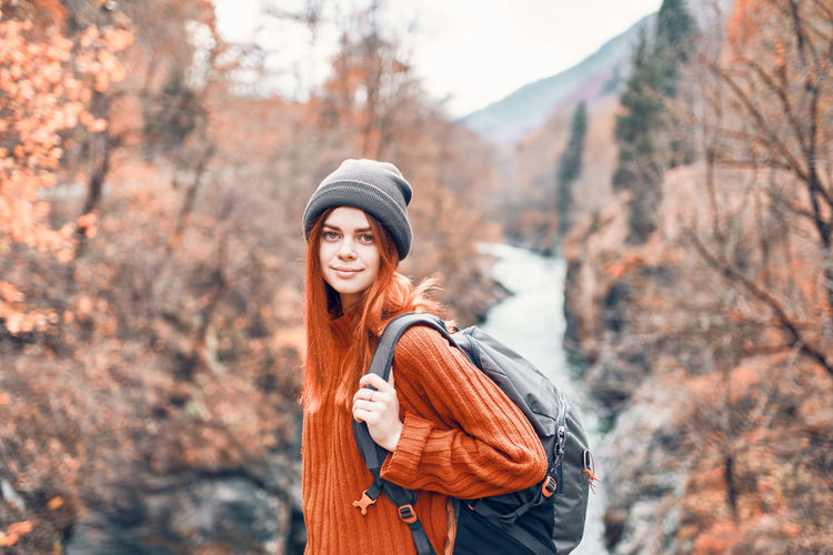 Portrait of woman wearing hat standing against trees