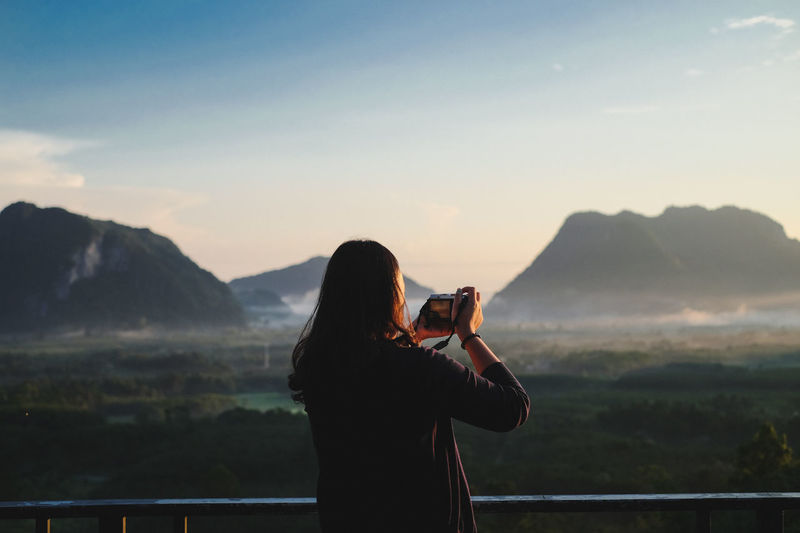 Rear View Of Woman Photographing Mountain Against Sky