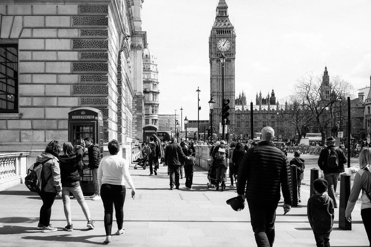 Rear view of people walking on street by big ben against clear sky